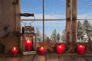 Country christmas decoration: wooden window decorated with red candles and latern. View to the mountains.